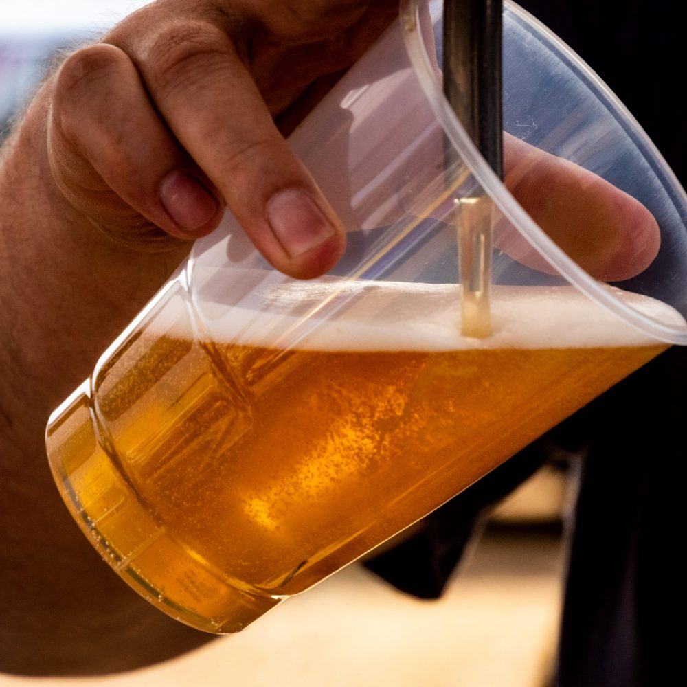 person-pouring-beer-on-clear-cup-1301390